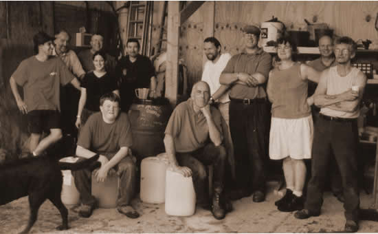 The first year's team pose for a photo around the barrels containing our first juice